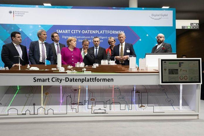 canciller alemana, Angela Merkel, y su ministro de Transporte, Andreas Scheuer, en una presentación de la Cumbre Digital el 29 de octubre de 2019 en Dortmund