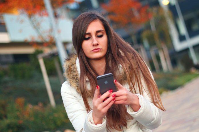 Chica mirando su teléfono móvil mientras pasea por la calle